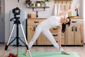 Beautiful girl in sportswear does yoga and shoots video for her blog photo