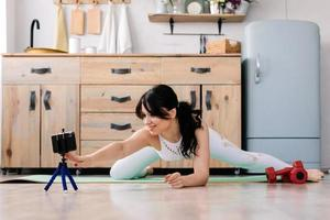 Young sportswoman doing leg stretches on a sports rug photo