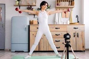 Beautiful, attractive girl trains hands with dumbbells photo