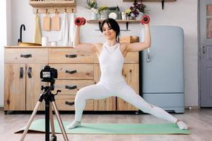 Online training. Joyful young woman making exercises while recording a video of a training photo