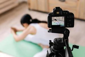 Attractive young woman practicing yoga and shooting video photo