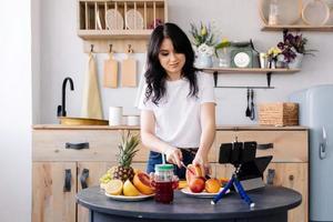 Attractive girl prepares fruit smoothies photo