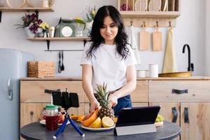 Beautiful girl prepares delicious healthy food and shoots video for her blog photo