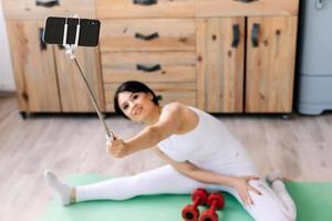 A girl takes a selfie while sitting on a string on a rug photo