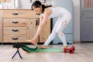 Sports girl puts a gym mat and dummblets photo