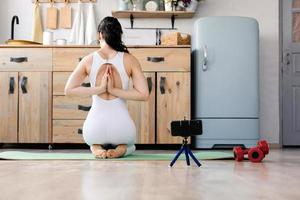 Young girl doing yoga fitness exercise at home photo