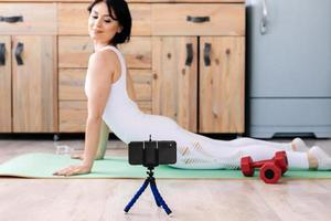 Attractive young fitness woman wearing sportswear doing stretching exercises, using fitness mat photo