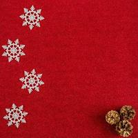 Fondo rojo de año nuevo con conos y copos de nieve. foto