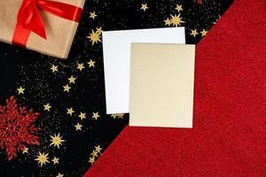 sobre un fondo festivo, rojo-negro, de año nuevo hay tarjetas de felicitación y un regalo foto