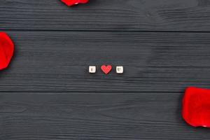 On a wooden background, the phrase I love you with cubes with letters and red rose petals. photo