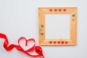 Wooden frame decorated with hearts and lined heart with red ribbon on a white background. Valentines day concept photo