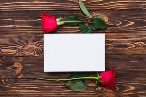 Red roses and blank piece of paper on wooden board, valentines day background, wedding day photo