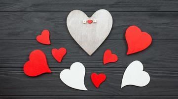 Hearts are laid out on a dark wooden background. photo