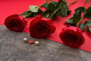 On a gray-red background there are red roses and cubes with letters laid out, the phrase I love you photo