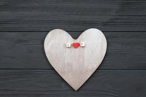 Wooden heart lies on wooden background. Love events concept, valentines day photo