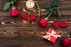 San Valentín u otro regalo navideño hecho a mano con corazones rojos y caja de regalos en envoltorio navideño. presente la decoración de la caja de regalo en la vista superior de la mesa de madera con espacio de copia, espacio vacío para el diseño. foto