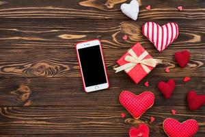 Flat lay cute composition with handmade fabric red hearts and mobile phone. Red gift box on wooden table. Happy birthday or anniversary congratulation. Romantic love story template with copy space. photo