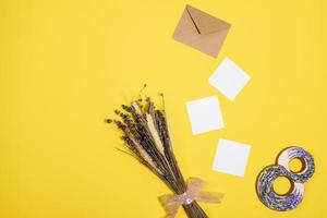 white sheets, envelope, figure eight, a bunch of dry grass lie  on a yellow background photo