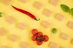Delicious ingredients for an Italian dish arranged on a yellow background. photo
