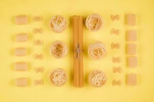 Assorted types of pasta on yellow background. Various forms of pasta. photo