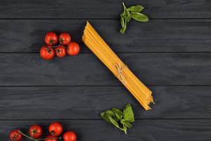 sobre un fondo oscuro están los ingredientes italianos. pasta, tomates, albahaca foto
