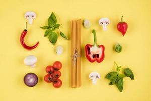 concepto de cocina italiana. sobre un fondo amarillo, un conjunto de ingredientes, pasta, tomates, pimientos, champiñones, albahaca foto