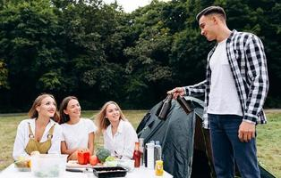 Man standing next a tent holding a beer and looking on the women outdoor in the camping photo
