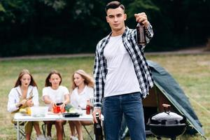 Man standing holding a beer and looking at the camera outdoor in the camping photo