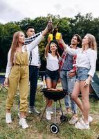 una compañía de amigos levantando botellas con una cerveza en el camping. - imagen vertical foto