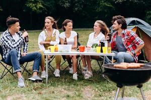 una compañía de amigos almuerza en el camping foto