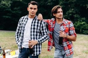 Two guys holding a beer and standing in the camping . - Image photo