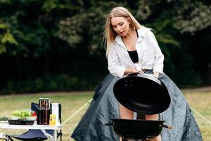 Woman preparing food on barbecue outdoor in the camping photo
