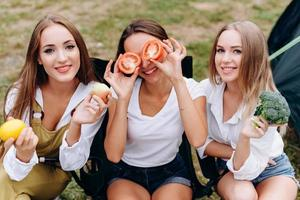 Three women are sitting and holding a vegetables and happily smiling photo