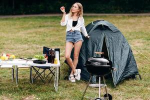 niña de pie en el camping sosteniendo una manzana y sonriendo juguetonamente foto