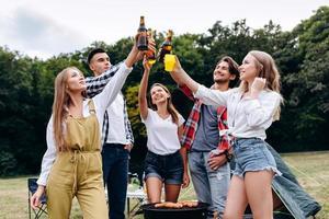 una compañía de amigos levantando botellas con una cerveza en el camping. - imagen foto