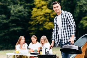 Young guy standing with the lid of the barbecue in his hand and looking at the camera photo
