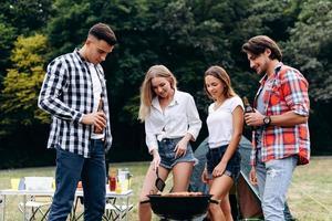 chicos de pie junto a una barbacoa. Chicas cocinando y hombres sosteniendo una cerveza y sonriendo. foto