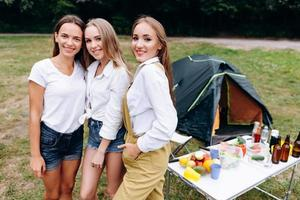 Three nice girls standing in the camping and looking at the camera photo