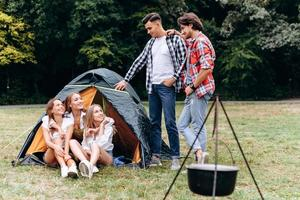 una compañía de amigos al lado de la carpa. - concepto de camping foto