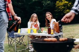 Smiling women sitting at the table with fresh food and looking on the barbecue photo