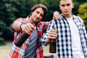 dos chicos sosteniendo una cerveza y mostrándola a la cámara en el camping. - imagen foto