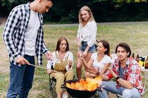 amigos en el campamento cocinando comida a la parrilla foto