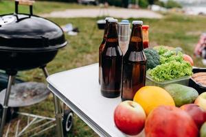 cerveza, salchichas y verduras frescas en la mesa al aire libre junto a la barbacoa foto