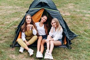 Nice women sitting next the tent in the camping  and posing at the camera photo