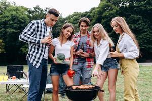 una compañía de amigos con una bebida y comida cocinando en la barbacoa del camping. - imagen foto