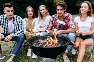 una empresa de amigos en el campamento cocinando comida a la parrilla. fondo borroso foto