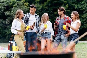 una compañía de amigos en el campamento levantando una botella de cerveza y divirtiéndose en el campamento foto