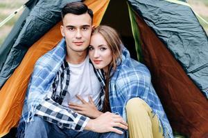 Una pareja encantadora sentada y abrazándose en la carpa al aire libre y mirando a la cámara foto
