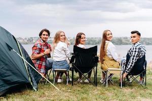una compañía de amigos se divierte en el camping. ellos sentados media vuelta. - vista trasera foto