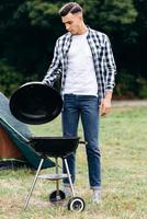 Young guy cooking  in the camping. Standing and  opens the lid of the barbecue photo